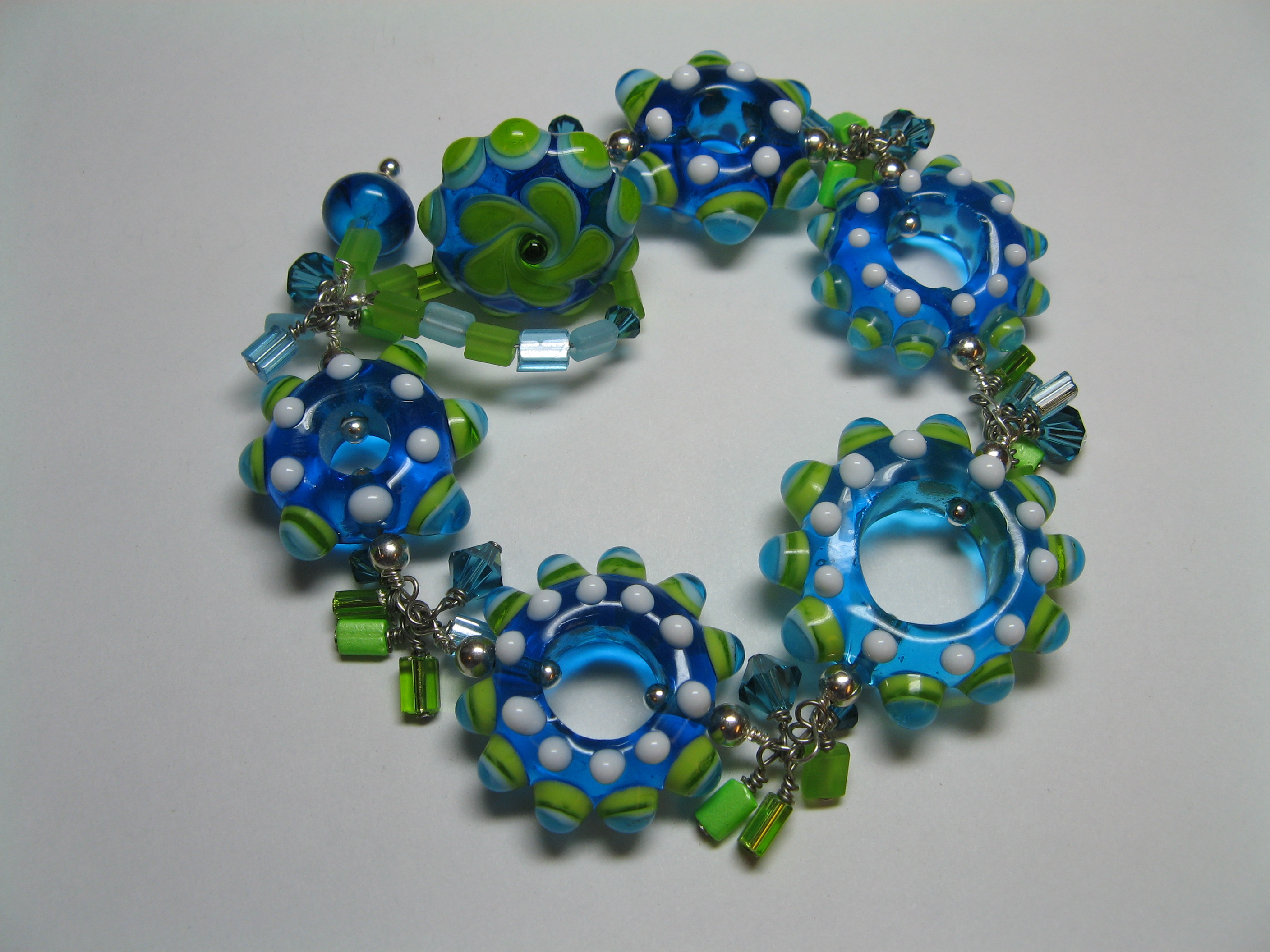 Bright blues and greens with a hand made button toggle